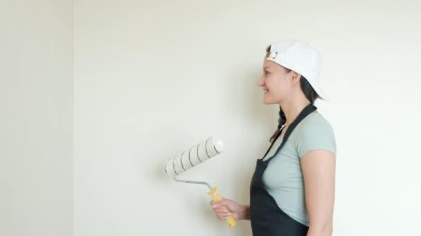 Wände mit Walze streichen. Eine junge Frau bemalt in ihrem Haus mit einer Walze Wände in Beige. Nahaufnahme.