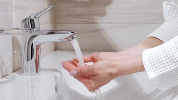 A woman in a white robe washes her hands in the bathroom sink. Water flows from the tap.