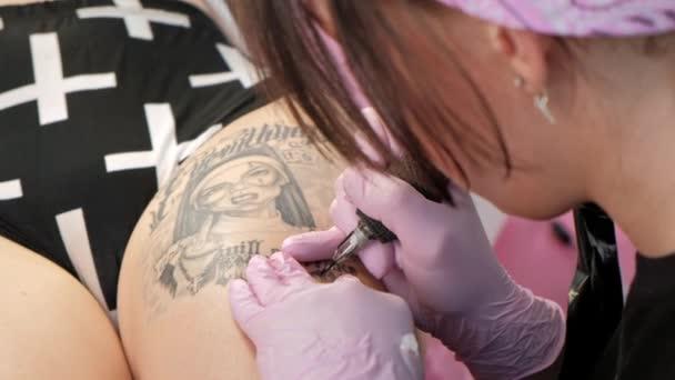 Tetoválás mester vonzó nő raszta tetoválások ügyfél a lány a csípő. Fekete tetoválás gép és tinta. Kép egy dühös apáca. Rózsaszín és fehér stúdió falháttér.