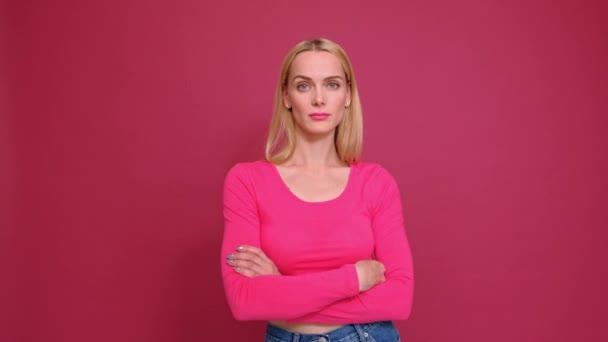 attraktive junge blonde Frau in rotem T-Shirt und Jeans, die auf rosa Hintergrund posiert. zeigt unterschiedliche Emotionen, Überraschung, Freude, Traurigkeit.