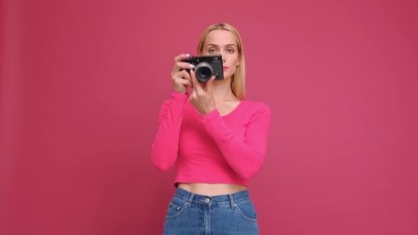 attraktive junge blonde Frau in rotem T-Shirt und Jeans, die auf rosa Hintergrund posiert. Fotos auf einer spiegellosen Kamera im Retro-Stil und lächelnd.