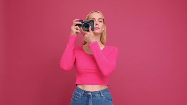 Attractive young woman blonde in a red T-shirt and jeans posing on a pink background. Photographs on a mirrorless camera in retro style and smiling.