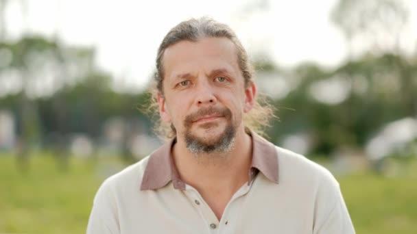 A nyugodt vonzó középkorú férfi hosszú, szürke hajú néz a kamerába, mosolyog, és nevet.