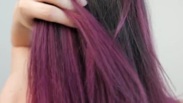 Portré egy fiatal nő egy fehér háttér. Hosszú festett haj. Ombre, színes festés. Lila és kék.