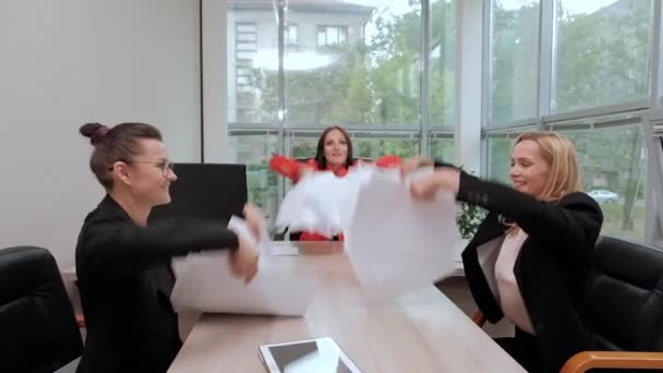 Three beautiful young girls in business suits are sitting at the office desk. Tired of work. Throw paper airplanes, and laugh. Break and rest.
