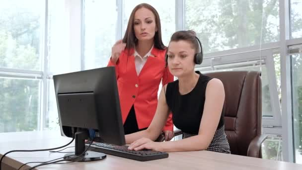 Two young women work in a bright office at the computer. Discuss workflows and enjoy a successful deal. Head and subordinate.
