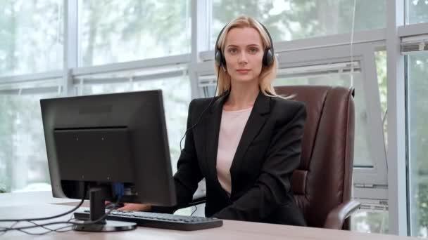 Mladá atraktivní žena v černém kabátě v černé bundě sedí u stolu ve výkonné židli. Pořádá videokonferenci ve sluchátkách s mikrofonem.