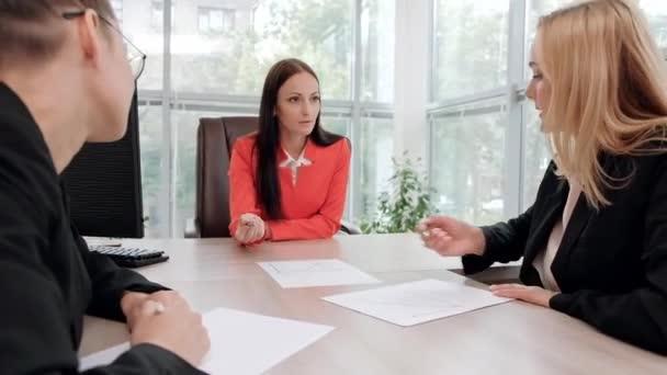 A három fiatal, vonzó nő üzleti öltönyök ül egy íróasztal és megvitatása munkafolyamatok. Fej és beosztottak. Szakemberek és kollégák dolgozó csapata.