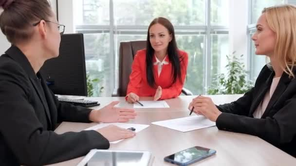 Three young attractive women in business suits are sitting at a desk and discussing workflows. Head and subordinates. Working team of professionals and colleagues.
