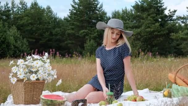 Mladá krásná blonďatá žena v klobouku a šatech si pije limonádu z ohrady, zatímco sedí na plži na zelené trávě. Piknikový koš, kytice sedmikráků, meloun.