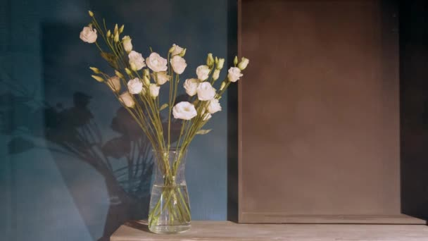 Glass vase with gently pink carnations stands on a wooden table against the background of the wall. Part of the interior.