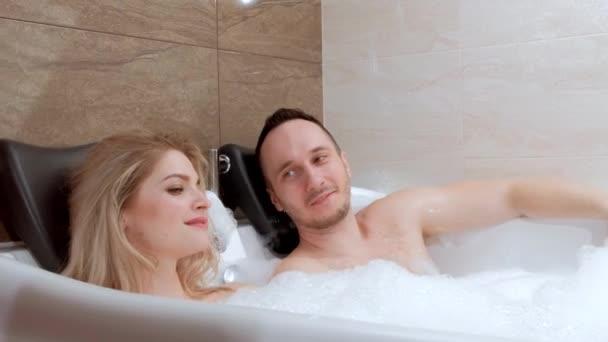 Mladý pár, muž a žena, leží ve vaně s pěnou. Relaxovat a v hotelu.