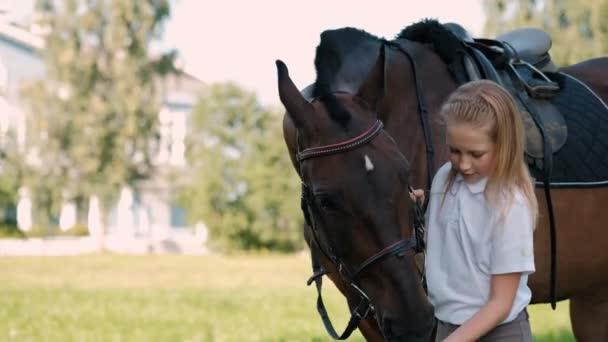 Lány tinédzser sétál a pályán egy barna ló.