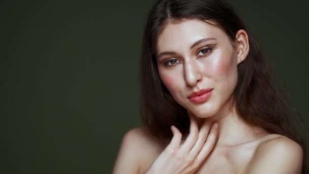 Eine schöne junge Frau mit langen lockigen schwarzen Haaren, Brustporträt, nackten Schultern. Schöne natürliche Haut. Rote Lippen und anmutige Hände. Mädchen posiert im Studio vor olivem Hintergrund.