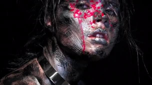 Fashion glamour portrait of beautiful young caucasian woman on black background. Bright colored creative makeup. Dramatic dark image. Effect of a dirty face with drops of blood.