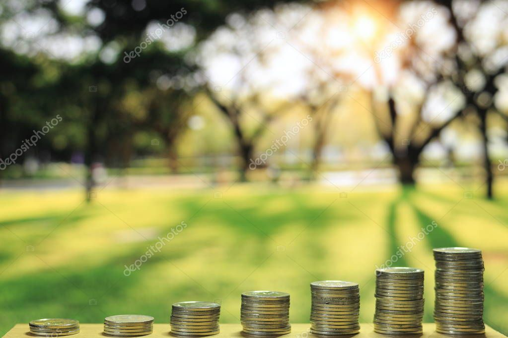 green and environmental funding. saving coin tower amount to an increasing chart graph on out of focus green park environment background with sun beam.
