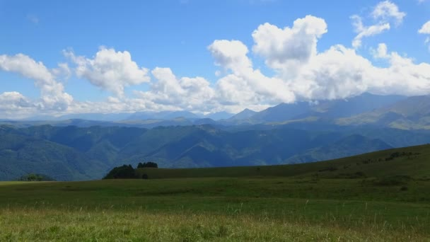 Panoramic view of mountains under blue cloudy sky in national park Dombai, Caucasus, Russia