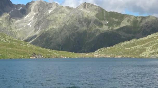 Malebný pohled na hory a modré jezero ve švýcarských Alpách