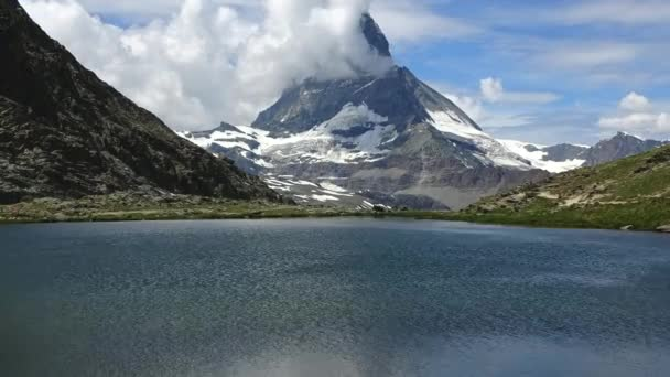 Time lapse view of group of people with snowy Matterhorn peak on background and lake Stellisee, Swiss Alps, Switzerland