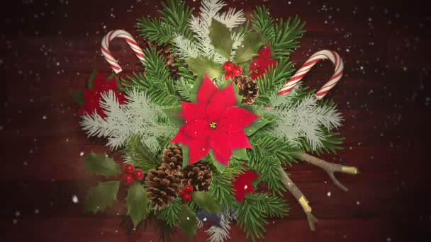 Animovaný closeup bílé sněhové vločky na cukroví a zelené vánoční větve, dřevěné pozadí