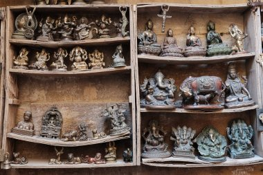 Many old statuettes on wooden shelves