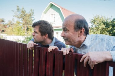 two caucasian men carefully watching over the fence.