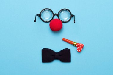 Funny glasses, red clown nose and tie lie on a colored background, like a face.