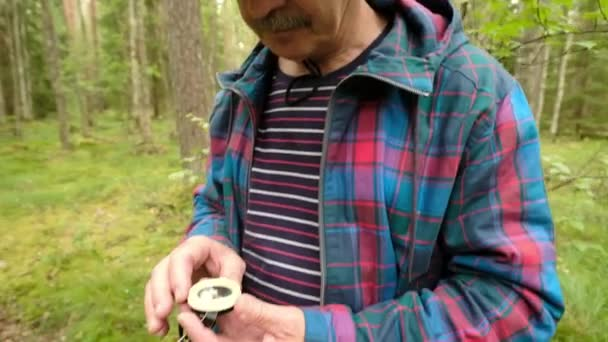 Man explorer searching direction with compass in summer forest