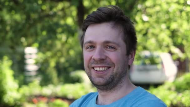 Elégedett mosolygós fiatal férfi a szabadban
