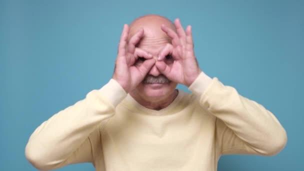 Idősebb férfi tartja ujjait közel szemek, mint a szemüveg vagy maszk, mint a szuperhős.