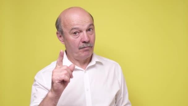 Strenger, reifer Mann zeigt Zeigefinger nach oben, gibt Ratschläge