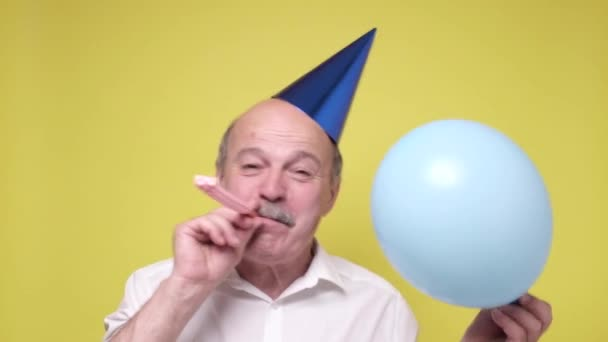 Idősebb férfi bulikalapban. Ünnepelünk. Buli van..