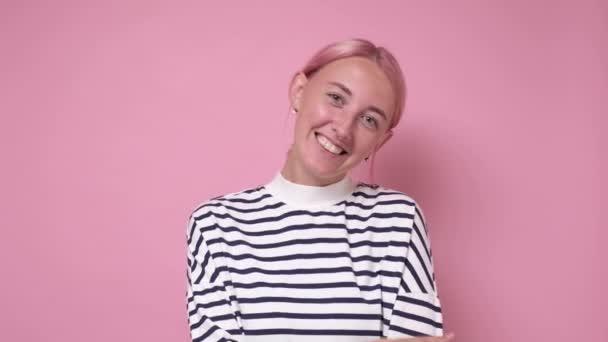 žena s okouzlujícím úsměvem a barvené růžové vlasy při pohledu do kamery