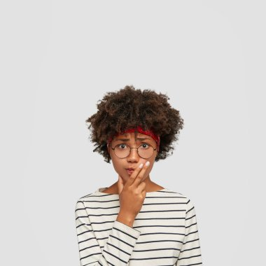 Indoor shot of worried black confused woman keeps hand on chin, looks with puzzled expression at camera, wears round spectacles, stands over white wall, blank copy space above. Nervous clueless girl
