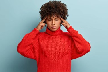 Distressed tired young woman massages temples, closes eyes tries to focus, has headache and migraine, dressed in red oversized jumper, isolated over blue background, keeps emotions under control