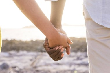 closeup of two lover hands stay together with a sunset backlight in background faraway. love and tenderness at the beach for man and woman young black race. life forever togetherness concept