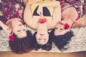 szép és gyönyörű három kaukázusi nők otthon. feküdt az ágyra keresnek fel a nagy mosoly és a boldogság. játszik a rózsa és a piros színű rúzs és a virágok. boldogság barátság koncepció kép