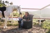 Kavkazská muž si svého koně na sedadlech venkovní na venkově. alternativní životní styl ve styku se zvířaty a přírodou. pes v pozadí