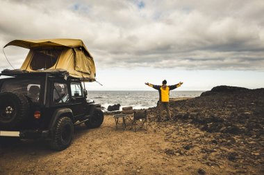 adventurer man in journey travel with off road car and roof tent to enjoy freedom and explorer concept. discover the world living near the power of the nature. ocean coast home view. driving all around
