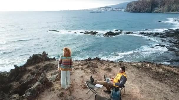nice couple enjoying a sunset at the end of the day. travel lifestyle in wanderlust for happy cacucasian people. working alternative office with laptop