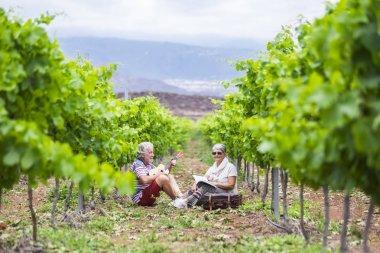 senior couple sitting in vineyard and man playing at ukulele acoustic guitar