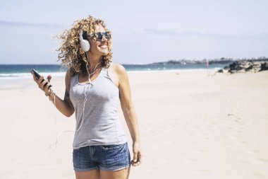 cheerful young woman enjoying vacation while listening music at beach