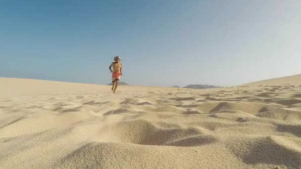 slow motion of boy jumping in sand on beach