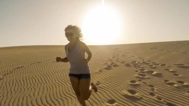 woman with curly hair running on sand