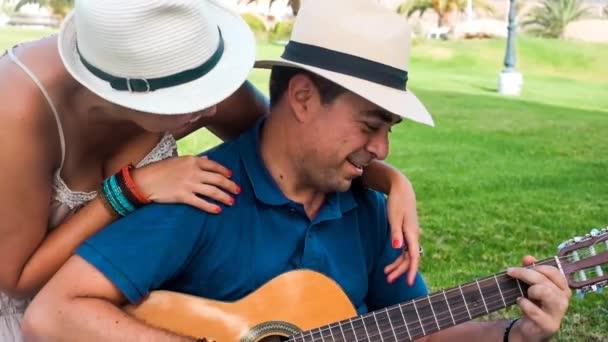 pár líbání v parku, zatímco muž hraje na kytaru