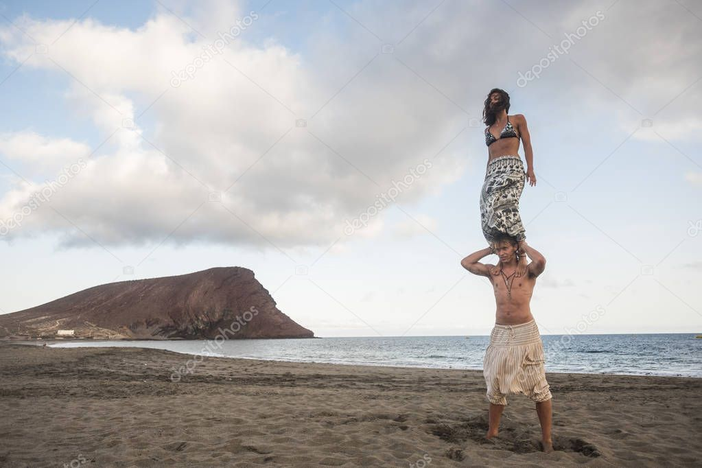 young man and woman making acrobatic balanced position at beach near ocean