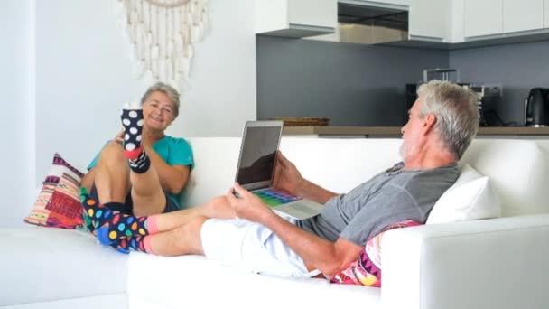 Älteres Paar mit Laptop und Smartphone zu Hause auf Sofa liegend