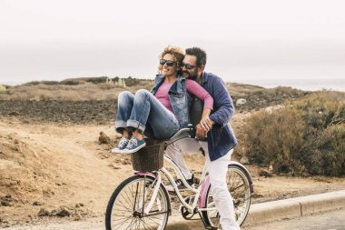 happy couple riding and having fun with bicycle outdoor