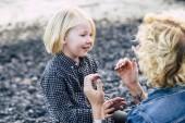 Paar Mutter und Sohn mittleren Alters und Kind spielen zusammen im Freien mit Liebe und Glück