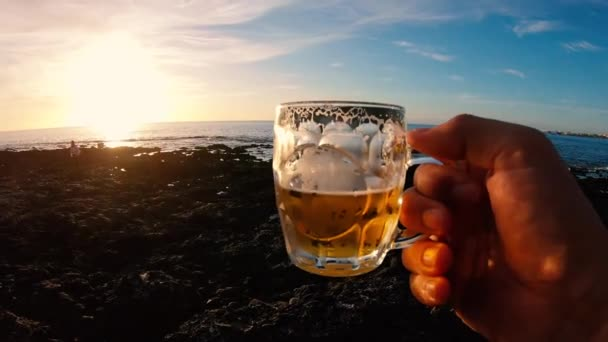 close up of male hand holding glass of beer on sunset background